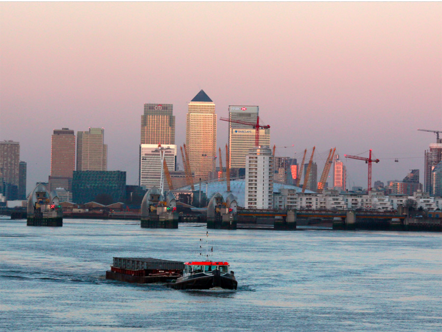 A tug pulls a container barge down the River Thames in front of London's financial district of Canary Wharf in the early morning January 24, 2015